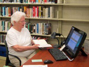 Library, Allison Butler checking out a book